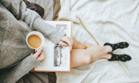 Dívka si dává kávu u knihy, tak vypadá správný odpočinek.